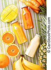fruit and vegetable smoothies in glass jars, orange mango banana carrot pineapple