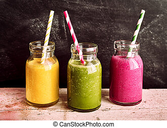 Side View Profile of Healthy Fruit and Vegetable Smoothies Served in Rustic Glass Jars with Colorful Striped Drinking Straws on Wooden Table with Dark Background