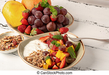 Fruit berry salad with yogurt and granola for healthy breakfast