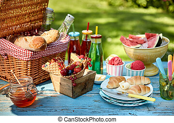 Fruit, bread, honey and ice cream on picnic table - Colorful...