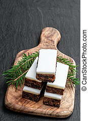 Fruit cake slices topped with marzipan on black stone background