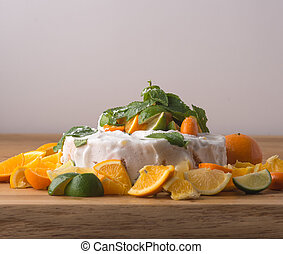 Fruit cake with cream, lime and oranges on table with light background