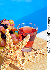 Fruit cocktail with grapes, blackberries and starfish.