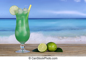 Fruit cocktail with limes on the beach and sea