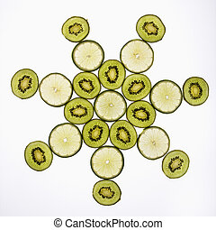 Fruit design. - Kiwi and lime fruit slices arranged on white...