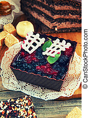 fruit dessert with black currant, brown form , decorated with chocolate, cinnamon, anise,