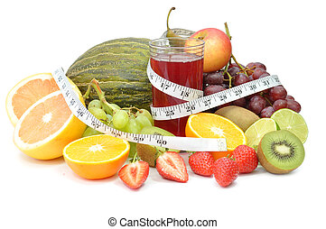 Fresh glass of juice surrounded by an assortment of fruit and a tape measure