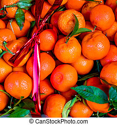 Fruit festive box. Fresh Tangerines (mandarines, clementines, citrus oranges) in a box with red ribbon. Harvest concept. Top view,