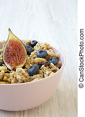 Fruit granola in pink bowl on a white wooden background, side view. Closeup.