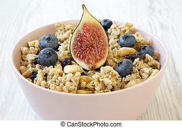 Fruit granola in pink bowl on a white wooden table, side view. Close-up.