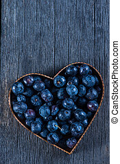 Fruit heart shape of blueberries from above on wooden background