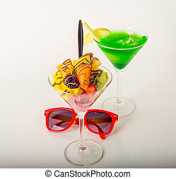 Fruit ice cream, decorated with fresh fruit, chocolate covered, green drink, martini glass, sunglasses