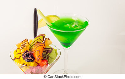 Fruit ice cream, decorated with fresh fruit, chocolate covered, green drink, martini glass
