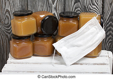 Fruit jam in jars. He is wearing a medical mask. Stands on a white-painted wooden box. Against the background of black pine boards.