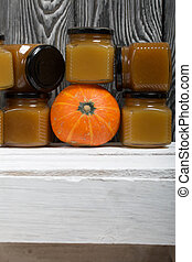 Fruit jam in jars. Nearby is an orange pumpkin. Stands on a white-painted wooden box. Against the background of black pine boards.