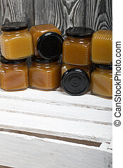 Fruit jam in jars. Stands on a white-painted wooden box. Against the background of black pine boards.