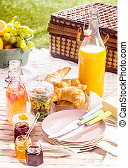 Fruit juice, croissants and fruit for a picnic