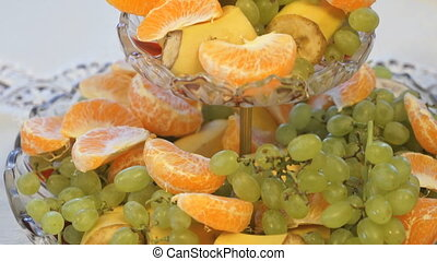 Fruit on plate with banana, tangerine, grape - Fruit on the...