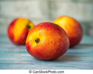 Fruit on the table. Three ripe yellow red nectarines