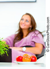 Fruit platter on table and smiling woman sitting on sofa  at home in background