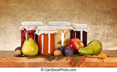 Compotes and jam in glass bottle with fresh fruits on wooden board