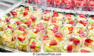 Fruit salad arranged in plastic cups for sale. Selective...