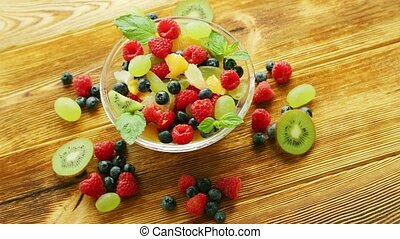 Fruit salad in bowl on table - From above glass bowl with...
