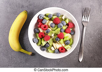 fruit salad in bowl with blueberry, kiwi, raspberry and banana