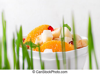 Fruit salad. Look through sprouted grass