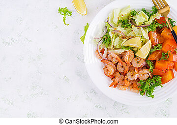 Fruit salad with fried prawns / shrimps, persimmon, red onion and lettuce in white bowls. Appetizers, snack, brunch. Healthy food. Top view, overhead, copy space