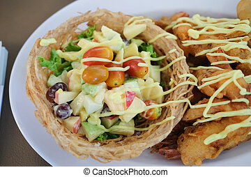 Fruit salad with fried shrimp in taro basket
