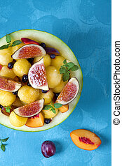 Fruit salad with yellow watermelon, fig, nectarine, plum, bilberry, apple, banana and honey