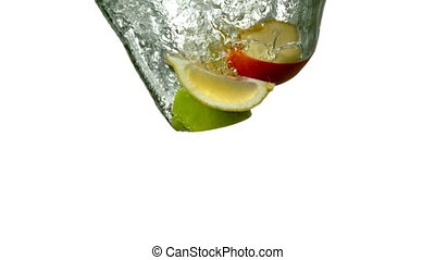 Fruit segments plunging into water on white background in...