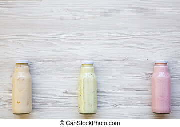 Fruit smoothies of different colors in glass jars on white wooden background. Top view, from above. Copy space.