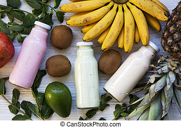 Fruit smoothies of different colors in glass jars with ingredients on white wooden background, top view. From above. Flat lay.