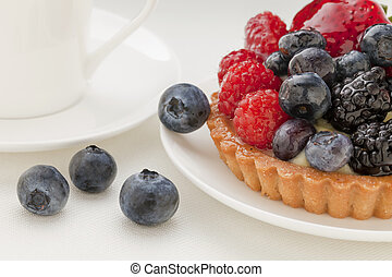 fruit tart with blueberry, blackberry, raspberry and strawberry, a coffee cup in background