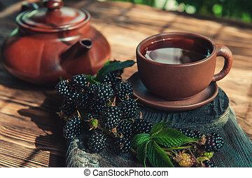 Fruit tea in a Cup with blackberries. Tea is made from berries and leaves of black raspberries