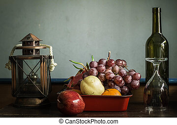 Fruit tray with a glass lamp on the table.