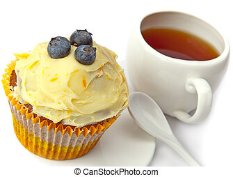 Fruitcake with a berry and a cup of tea