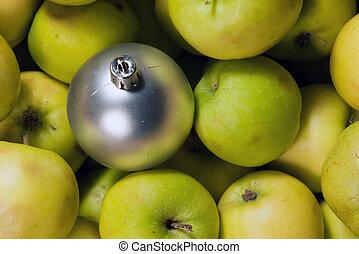 Fruitful new year. Gray xmas ball on a green apples