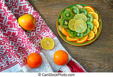 Fruits and beautiful old towel on the table surface.