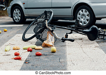 Fruits and broken bike on pedestrian crossing after collision with a car