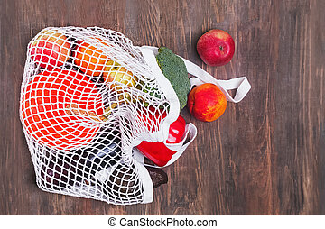 Fruits and vegetables from farmer's market in reusable shopping bag on the wooden table