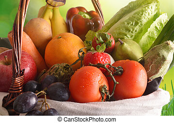 Fruits and vegetables in a wicker basket with green background