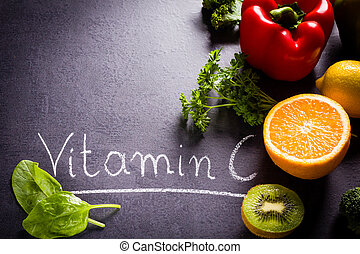 Fruits and vegetables rich in vitamin C with white word inscription by chalk and copy space on black slate.