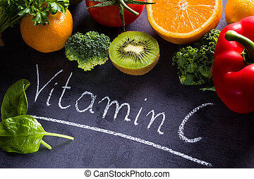 Fruits and vegetables rich in vitamin c with white word inscription by chalk.