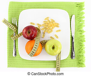 Fruits and vitamins with measuring tape on a plate