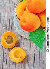 fruits apricot in basket on wooden background