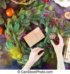 fruits, box with a gift in gray paper in the hands of a woman and a green Christmas tree on a blue wooden background