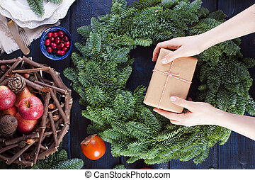 fruits, box with a gift in gray paper in the hands of a woman and a green Christmas tree on a blue wooden background.
